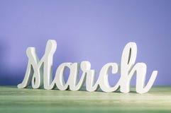 Marzo - el biginning del concepto de la primavera Inscripción tallada de madera en fondo rosado púrpura u oscuro Foto de archivo libre de regalías