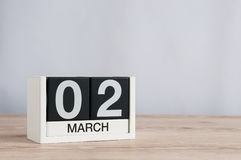 2 marzo Giorno 2 del mese, calendario di legno su fondo leggero Tempo di primavera, spazio vuoto per testo Immagine Stock