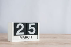 25 marzo Giorno 25 del mese, calendario di legno su fondo leggero Tempo di primavera, spazio vuoto per testo Fotografie Stock