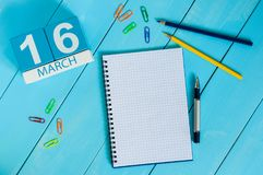 16 marzo Giorno 16 del mese, calendario sul fondo di legno blu della tavola con il blocco note Tempo di primavera, spazio vuoto p Immagini Stock