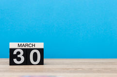 30 marzo Giorno 30 del mese, calendario sulla tavola con fondo blu Tempo di primavera, spazio vuoto per testo Fotografia Stock Libera da Diritti