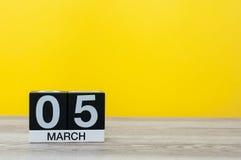 5 marzo Giorno 5 del mese, calendario sulla tavola con fondo giallo Tempo di primavera, spazio vuoto per testo Immagine Stock Libera da Diritti