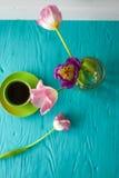 8 marzo, giorno del ` s della madre, tazza di caffè e tulipani su fondo blu Fotografia Stock