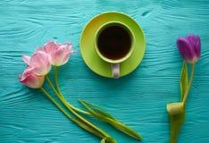 8 marzo, giorno del ` s della madre, tazza di caffè e tulipani su fondo blu Immagine Stock