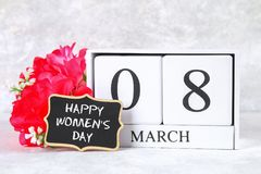 8 marzo, giorno internazionale del ` s delle donne Calendario perpetuo di legno, fiori rosa e lavagna Fotografia Stock