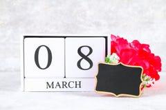 8 marzo, giorno internazionale del ` s delle donne Calendario perpetuo di legno, fiori rosa e lavagna Copi lo spazio Fotografia Stock