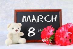 8 marzo, giorno internazionale del ` s delle donne Lavagna con i fiori e l'orsacchiotto rosa Fotografia Stock Libera da Diritti