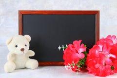 8 marzo, giorno internazionale del ` s delle donne Lavagna con i fiori e l'orsacchiotto rosa Copi lo spazio Fotografia Stock