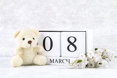 8 marzo, giorno internazionale del ` s delle donne Un calendario perpetuo di legno ed i fiori bianchi, orsacchiotto Immagini Stock