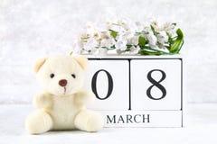 8 marzo, giorno internazionale del ` s delle donne Un calendario perpetuo di legno ed i fiori bianchi, orsacchiotto Fotografie Stock Libere da Diritti