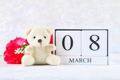 8 marzo, giorno internazionale del ` s delle donne Un calendario perpetuo di legno ed i fiori rosa, orsacchiotto Immagine Stock