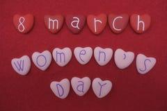 8 marzo, il giorno del ` s delle donne con rosso ed il rosa hanno colorato le pietre del cuore sopra la sabbia rossa Fotografie Stock
