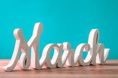 Marzo - palabra tallada de madera en el fondo de la turquesa A principios de marzo mes El resorte está viniendo Fotos de archivo libres de regalías