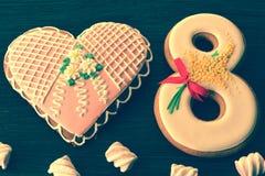 8 marzo pan di zenzero e cuore su un fondo d'annata bianco Immagini Stock