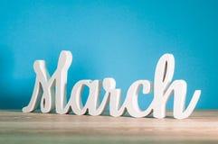 Marzo - 1r mes de la primavera Palabra tallada de madera en el fondo azul claro Carde para el día de madres, el 8 de marzo, Pascu Foto de archivo