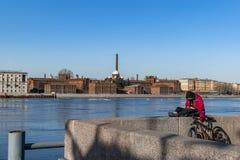 Marzo 2019 St Petersburg Fiume della città della primavera in Russia ragazza che riposa sull'argine del Neva sull'altra costa del immagine stock libera da diritti