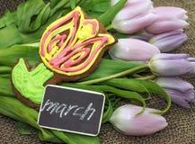 8 marzo Tulipani e dolce freschi nella forma di fiore Fotografia Stock