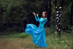 Marzy młodej kobiety w błękit sukni w lesie Zdjęcia Stock
