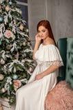 Marzycielska młoda piękna dziewczyna w białej wieczór sukni przeciw choinki tłu zdjęcia royalty free