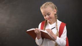 Marzycielska mała uczennica pisze w notatniku, robi pracie domowej przeciw blackboard zbiory wideo
