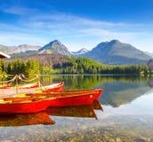 Marzycielski czerwony łódź stojak przy molem na spokojnym jeziorze Zdjęcia Stock