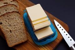 Masło i chleb pokrajać na desce obrazy stock
