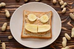 Masło orzechowe grzanka z bananów plasterkami na drewnianym tle obraz stock