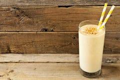 Masło orzechowe owsa bananowy smoothie z słoma nad nieociosanym drewnem Zdjęcia Stock