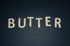 Masło pisać z kolorowymi drewnianymi listami na błękitnym tle Fotografia Stock