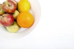 Maçãs frescas com laranja e limão na placa contra o fundo branco Fotos de Stock