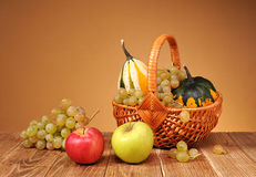 Maçãs, uvas e abóboras decorativas em cestas de vime Imagem de Stock