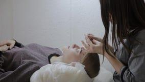 Masażysta stosuje twarzową masaż śmietankę młoda dziewczyna w piękno salonie zdjęcie wideo