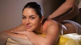 Masażysta robi masażowi piękna dziewczyna Ono uśmiecha się, wtedy spojrzenia przy kamerą 4K zwalniają mo zbiory wideo