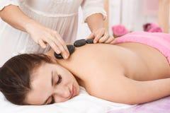 Masażysta robi masażowi z gorącymi kamieniami na kobieta plecy fotografia royalty free