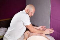 Masażysta wręcza robić masażowi, szyi i ręce kręgosłupa i plecy, Zrelaksowany pacjent cieszy się Mężczyzna wręcza masowanie kobie Obrazy Royalty Free