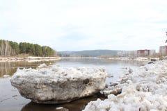 Masa de hielo flotante desechada en la orilla del río después de una deriva del hielo Foto de archivo libre de regalías