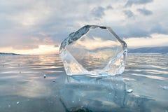 Masa de hielo flotante de hielo transparente en la superficie congelada con el cielo de la reflexión y de la puesta del sol Lago  Fotografía de archivo libre de regalías