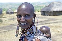 Masaai村庄运载婴孩,肯尼亚的生活妇女 免版税库存图片