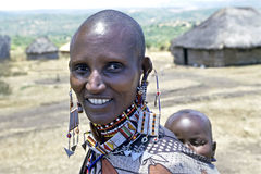 Masaai village life women carrying baby, Kenya. Kenya, Rift Valley, Masai Mara, village Entesekera: This Maasai mother with radiant smile and colorful beaded Royalty Free Stock Image