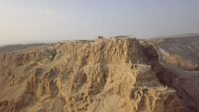 Masada front view from drone with funicular station. And end of snake path stock footage