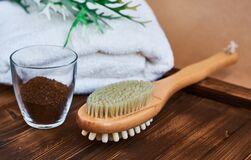 Free Masage Brush, Body Skin Care And Coffee Natural Scrub In Glass, White Towel And Greens On Dark Wooden Background. Royalty Free Stock Images - 183652719