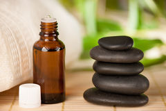 Masage rocks and bottle of aromatherapy oil. On a table Stock Images
