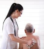 Masagging gamal man för sjuksköterska med rullmassageren Arkivfoton