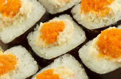 Masago Sushi Roll. Masago eggs seen close up on a rice roll with the nori sea weed on the outside Royalty Free Stock Photos