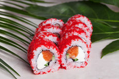 Masago Sushi roll Orange red Philadelphia cheese, salmon, green onion still life on trapicheskih Cunha leaves Japanese Royalty Free Stock Image