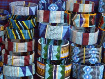 Masai bead bracelets. Piles of colourful bead bracelets made by Masai tribespeople of Tanzania. These attractive beaded bracelets are predominantly blue with red stock photos