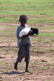 Masai Child with a Little Sheep. A young masai child bringing a little white and black sheep to his tribe, in Kenya. It describes the poverty of this people and Stock Photos