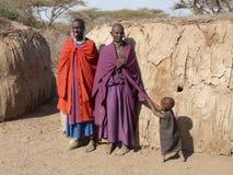 Masai erzieht mit dem Kind, das an der Kleidung der Mutter für Aufmerksamkeit zerrt Lizenzfreies Stockbild