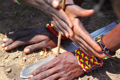 Masai Make Fire. The traditional masai method to produce fire rubbing two  pieces of wood Royalty Free Stock Image