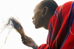 Masai male making fire by rubbing sticks together in village near Tsavo National Park, Kenya, Africa Stock Photography